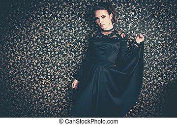 Beautiful young girl wearing black evening dress in luxury...