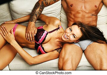 Young beautiful sexy couple in underwear lying on sofa