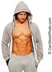 Handsome man in grey hoodie showing his abdominal muscles