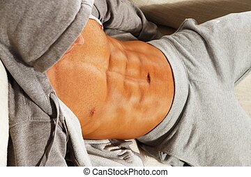 Sporty man in grey hoodie with muscular torso relaxing on...