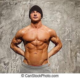 Handsome man with muscular torso in beanie hat posing
