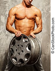 Handsome sporty man with muscular body holding alloy wheel