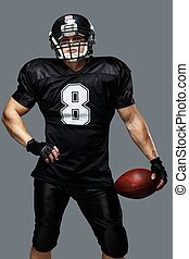 American football player with ball wearing helmet and jersey...