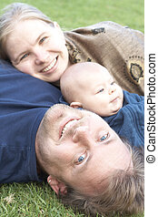 Happy family lying on the grass - Beautiful happy family of...