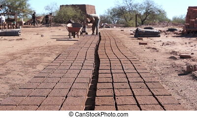 Adobe Brick Making Far Dolly - Long, dolly shot of a row of...