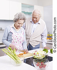 senior couple in kitchen - senior asian couple preparing...