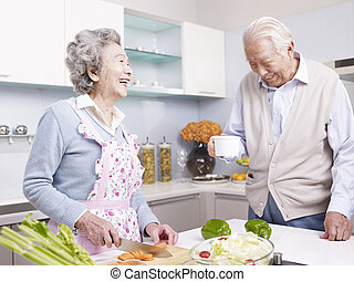 senior couple in kitchen - senior asian couple talking and...