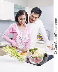 young couple in kitchen - young asian couple preparing meal...