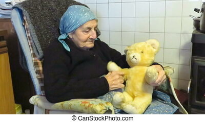 Teddy bear senior woman - Senior woman sitting with a fluffy...