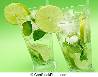 Two mojito cocktails on green background - Two mojito...
