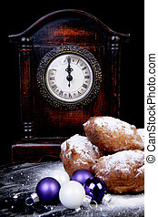 Dutch donut also known as oliebollen, traditional New Year's eve food, clock on midnight over black background
