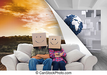 Composite image of silly employees with arms folded wearing boxes on their heads with smiley faces on a couch
