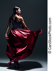 Young sexy dancing woman in red dress