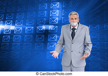 Composite image of businessman gagged with adhesive tape on...