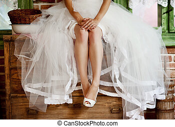 Detail of bridal legs with shoes sitting on the wooden table