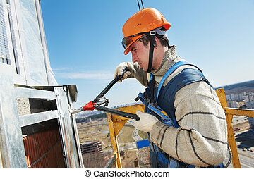 Worker builders at facade tile installation - worker builder...