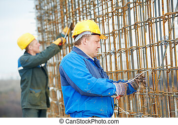 two construction workers making reinforcement - builder...