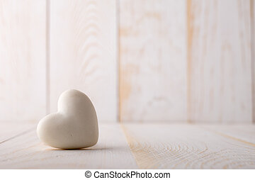 Stone heart. - Stone heart on the white wooden background.
