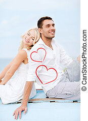 couple sitting on boat at sea side - summer holidays and...