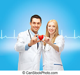 smiling doctors cardiologists with heart - healthcare and...