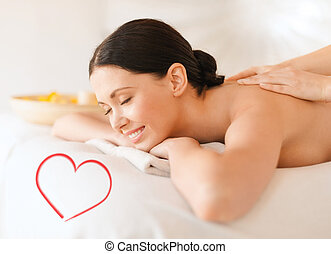 smiling woman in spa salon getting massage - health and...