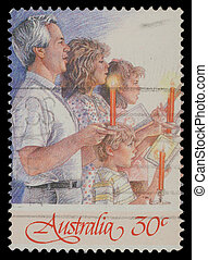 Christmas stamp printed in Australia shows family singing with candles