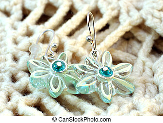 Transparent handmade earrings on the knitted background