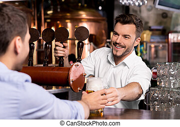 Here is your beer. Cheerful young bartender giving a mug...