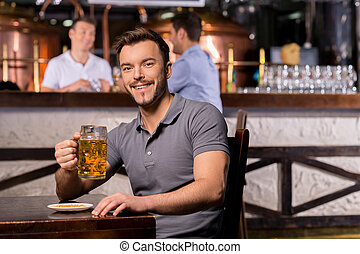 Man in beer pub Cheerful young man holding a beer mug and...
