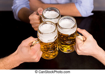 Cheers! Close-up top view of people holding mugs with beer