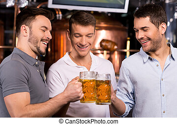 Old friends meeting. Three cheerful young men drinking beer...