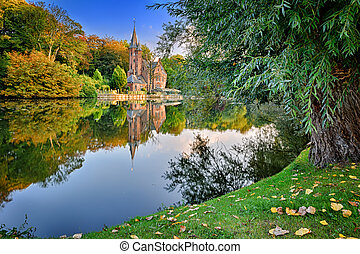 Autumn landscape with lake and old mansion. Bruges, Belgium