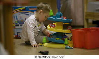 Little boy playing with a plastic parking garage - Little...