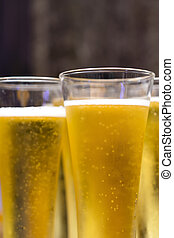Glasses of beer with bubbles floating and on top