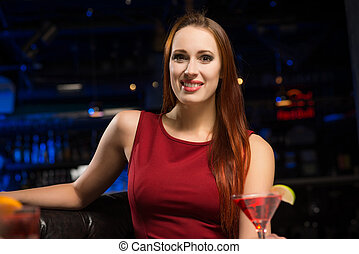 Portrait of an attractive woman in a nightclub, sitting on...