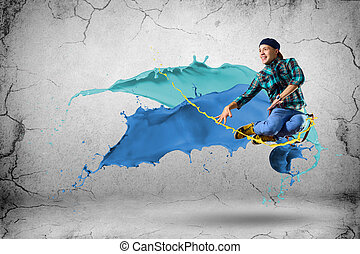 young male dancer jumping with splash of paint - young male...