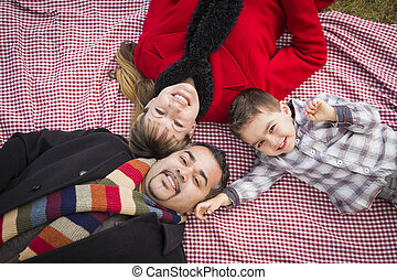 Family in Winter Clothing Laying on Their Backs in Park