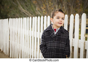 Young Mixed Race Boy Waiting For Schoold Bus Along Fence...