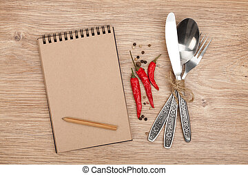 Blank notepad with pencil and silverware set on wooden table