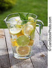 Pitcher with homemade lemonade on wooden table