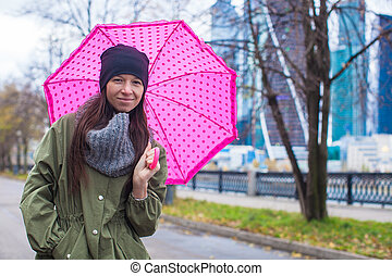 Young woman walking with umbrella in autumn rainy day