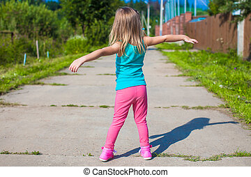 Little girl walking outdoor and having fun