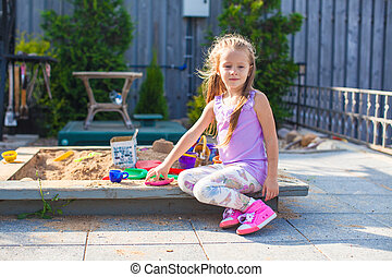 Little cute girl playing at the sandbox with toys in yard