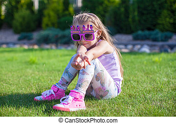 Adorable little girl with Happy Birthday glasses smiling outdoor