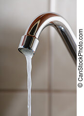 Tap with Water Flowing Slowly - Vertical image of a tap with...