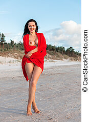 naked woman on a beach with red fabric