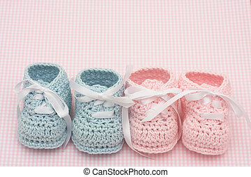 Baby Booties - Blue and pink baby booties on a pink...