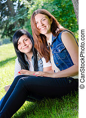 Two young female students sitting in park with tablet pc -...