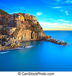 Manarola village, rocks and sea at sunset. Cinque Terre,...