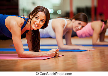 Cute girls working out in a gym - Happy female friends...